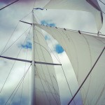 Full sails looking up at Clouds in a blue sky