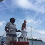Guest steering and captain of boat showing the way to go