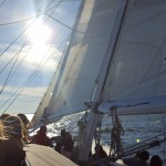 Guests on board sailing away into the bright blue sky
