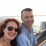 Smiling couple sitting on the deck of schooner with water behind them