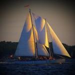 The schooner under full sail half in sunlight half in darkness