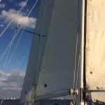 Looking through schooner sails at sailboats on the blue horizon