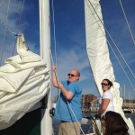 Guests lending a hand in raising the sails on board the schooner