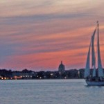 USNA in silhouette against a pinked streaked sky with sailboat on water