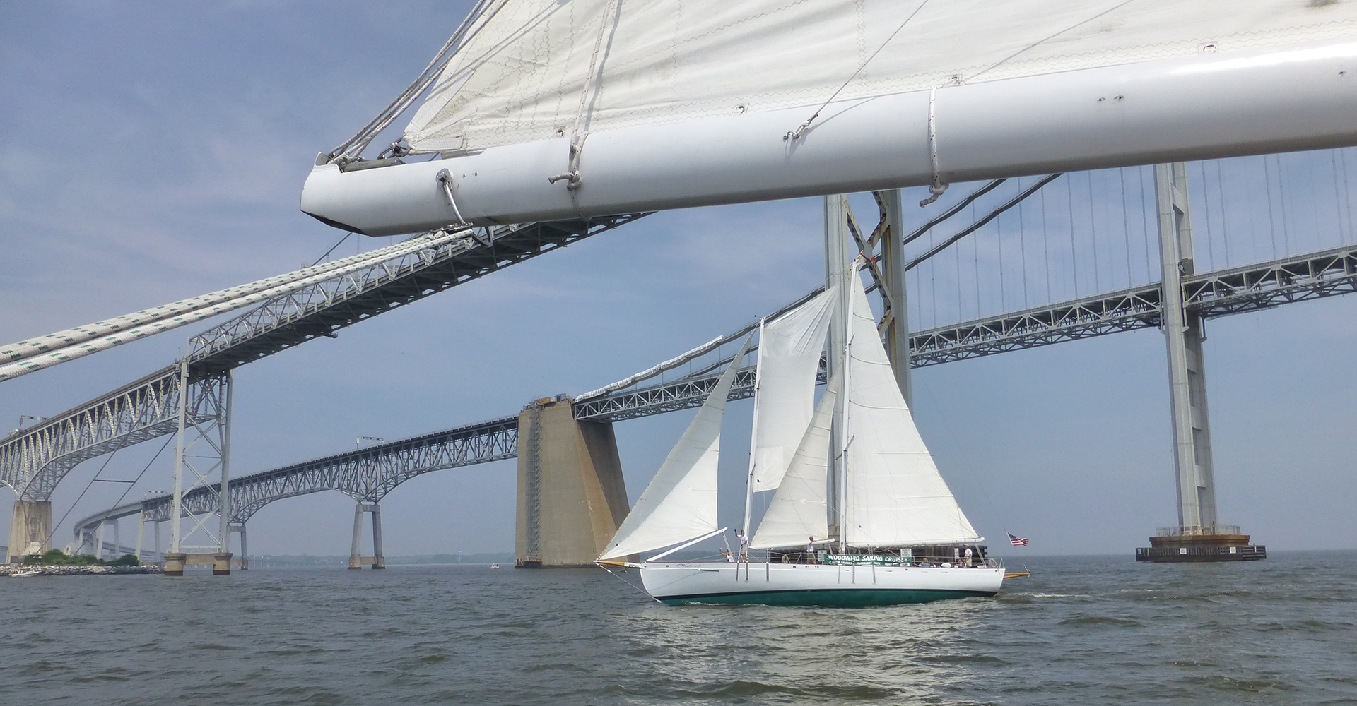 Looking from one schooner to the other schooner sailing in front of Bay Bridge