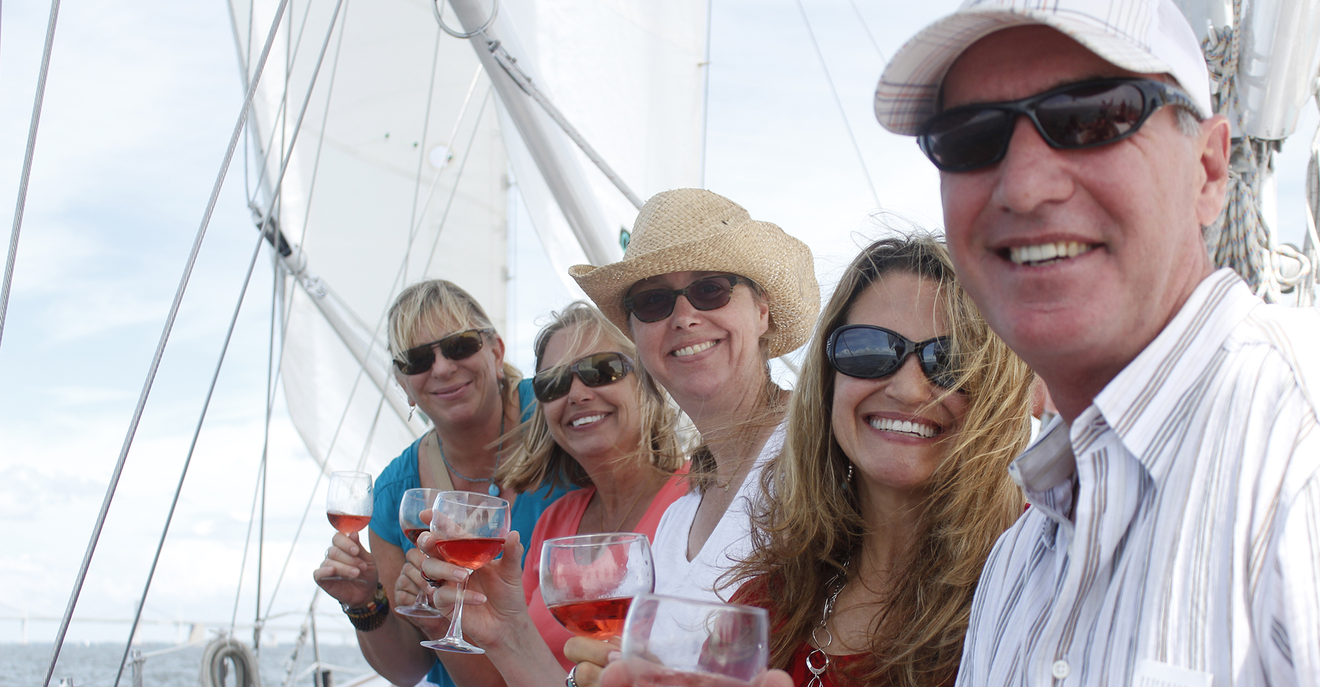 Guests with sunglasses and smiles enjoying glasses of wine on the boat