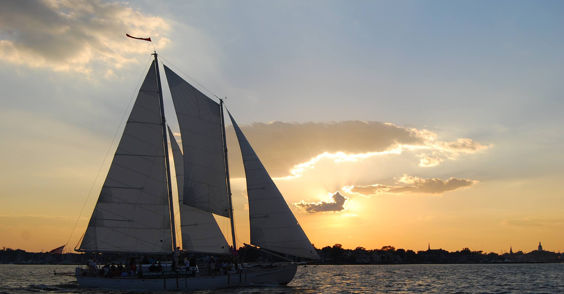 Schooner sailing with skyline and sunset over dark waters