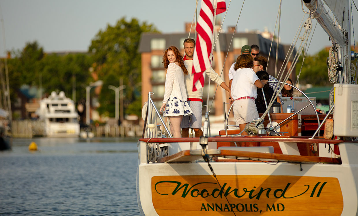 Couple posing at the stern of schooner with name Woodwind II Annapolis