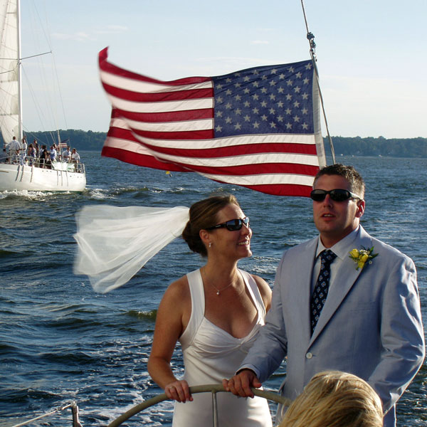 Bride and groom steering the boat with American flag in the background
