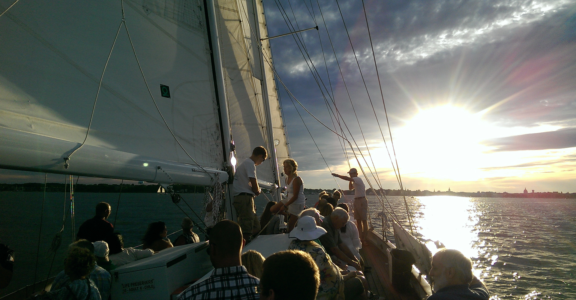 Guests on board sailing directly into brilliant sunset