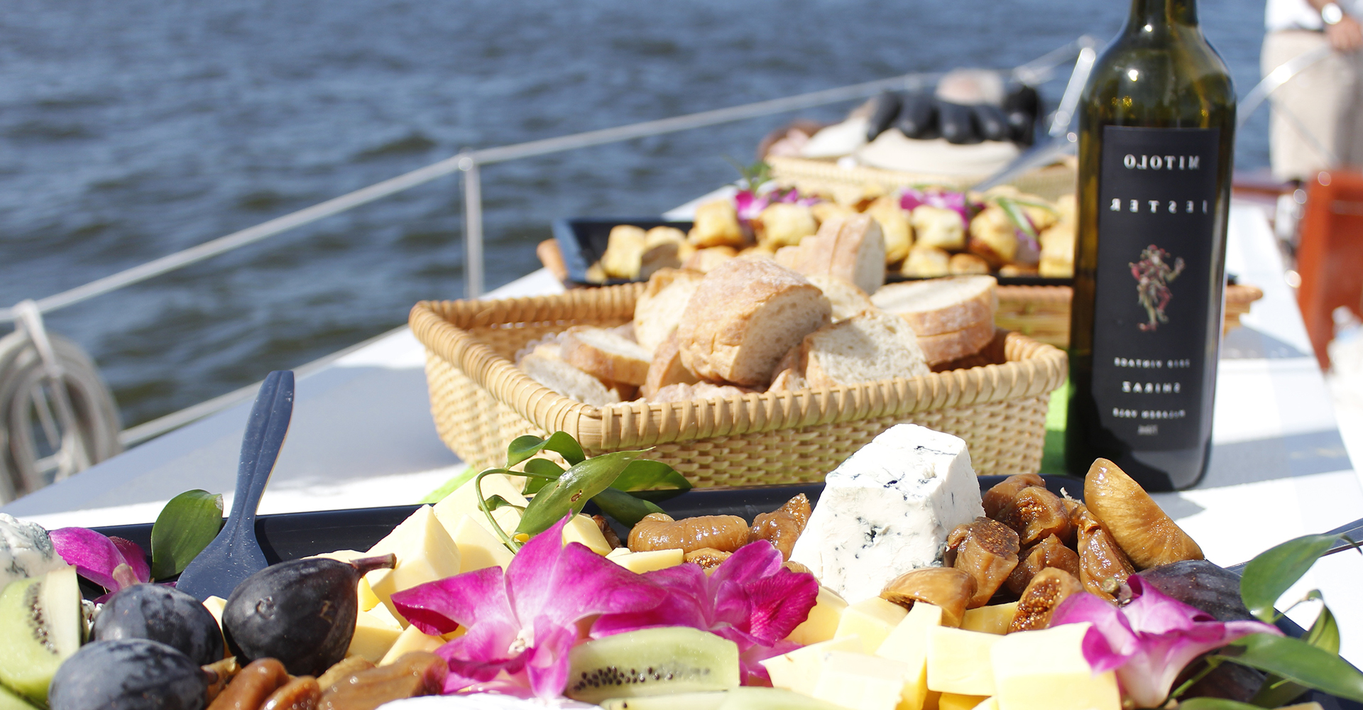 Cheese bread and wine displayed with flowers on the sailboat