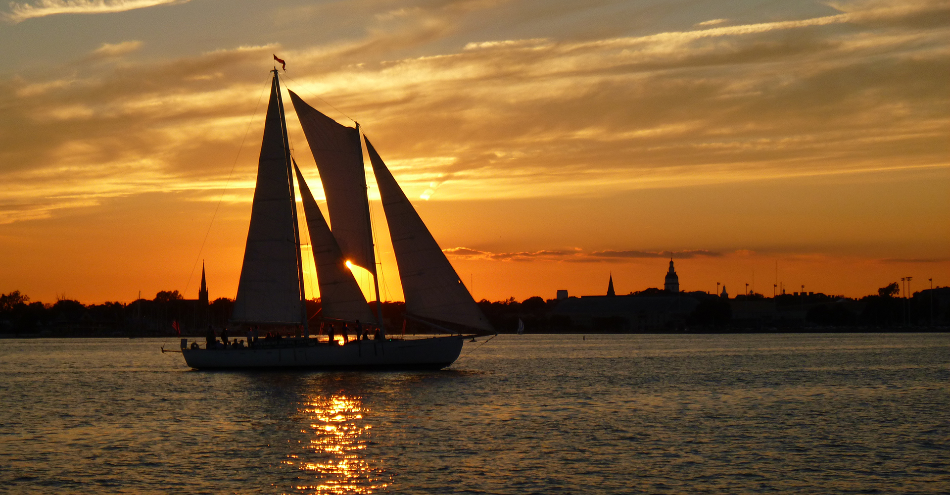 Schooner sailing in orange sunset in Annapolis