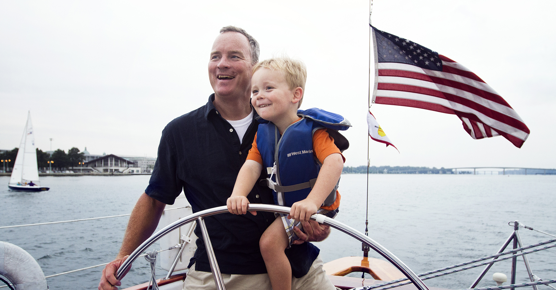 Father and son steering the helm and laughing