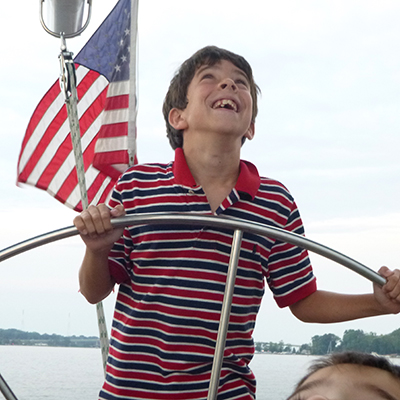Young boy looking up at the sails in a striped shirt while steering the boat