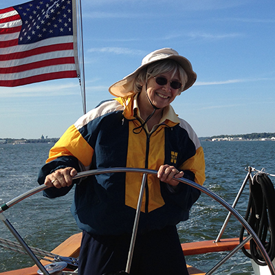 Guest in blue and gold jacket and a hat smiling and steering the helm