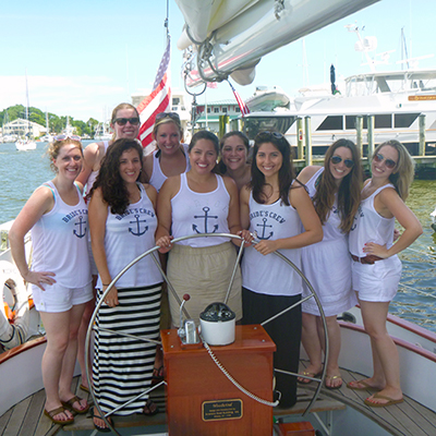 Young ladies all in white tops with blue anchors at the helm