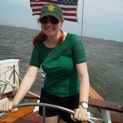 Young girl with red hair and green hat steering the boat