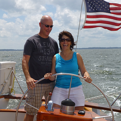 Smiling couple at the helm steering the schooner in the sun