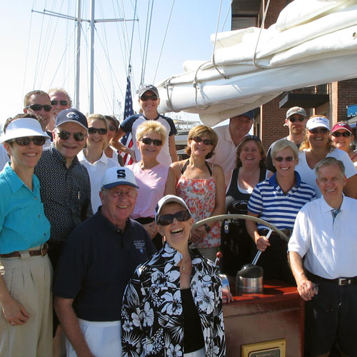 A group party on the schooner everyone smiling in the sun