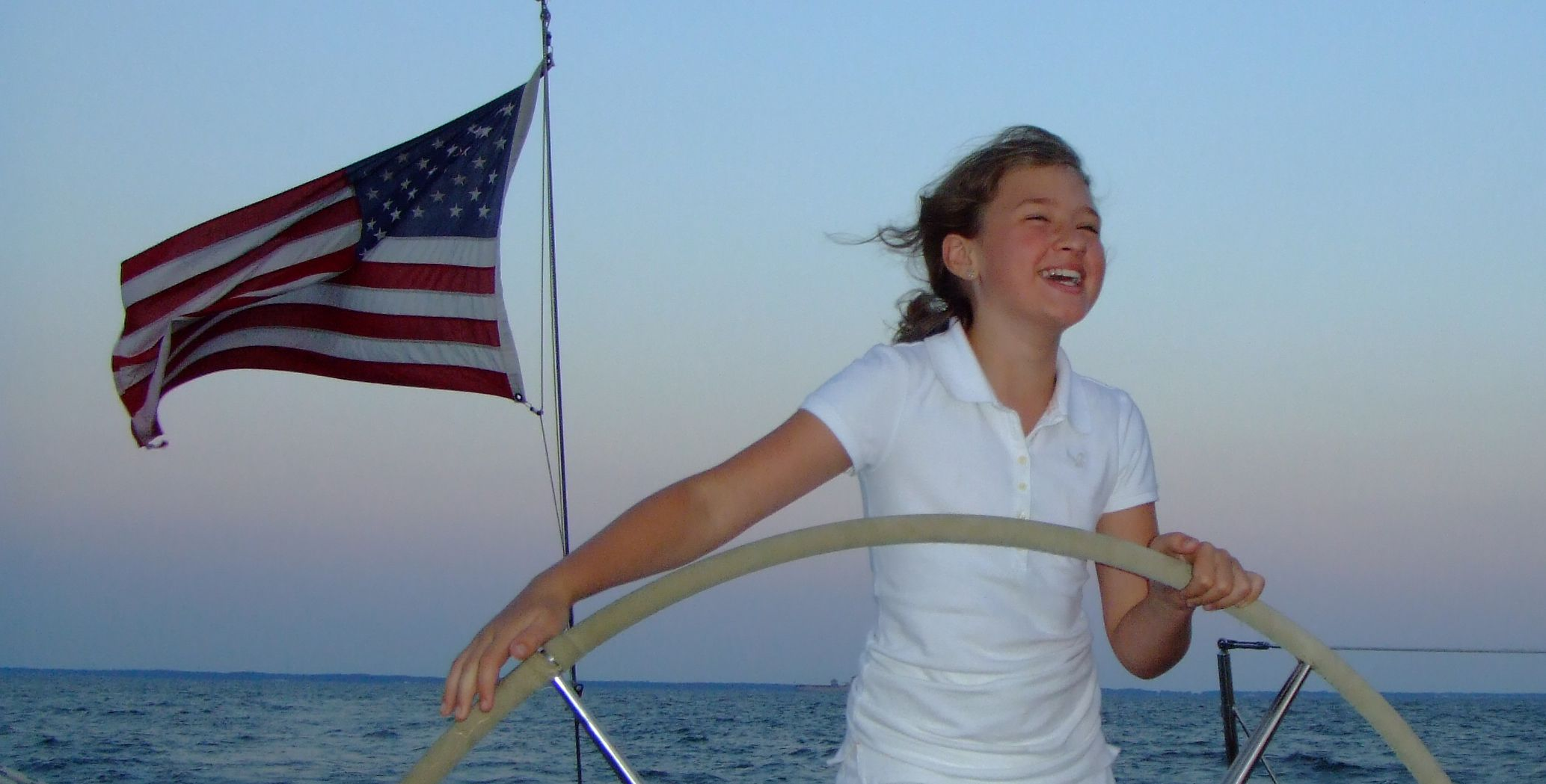 Girl steering the helm with joy on her face