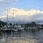 Reflection of boats docked in calm waters with blue sky and clouds
