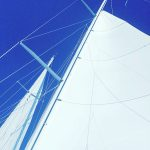 White sails against a brilliant clear blue sky