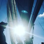 Looking up through schooner sails and rigging at bright sun