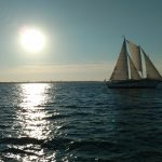 Schooner on an evening sail with bright sun reflecting on the water