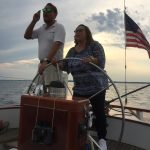 Captain sharing direction to sail with guest steering boat