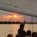 Guests looking on from boat as sunsets over Annapolis skyline