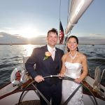 Bride and Groom steering the boat together with sunset behind them