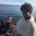 Women looking unsure about steering the big schooner with a smile
