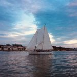 Schooner sailing in dark blue waters reflecting pinks and blues from sky