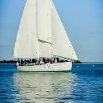 White Schooner standing out against bright blue sky and water