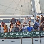Woodwind Sailing Cruises banner on the side of schooner with guests
