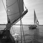 Black and white photo of schooner and a sailboat with sun on water