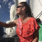 Pretty women in orange blouse smiling into the sun on a sail