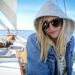 Pretty young women in hoodie and sunglasses sailing on a sunny day