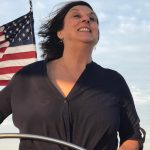 Women guest captaining the helm with American flag flying