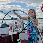 Small girl with sailboat sundress captaining the helm with a smile
