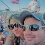 Couple smiling while captain sailing the boat in background