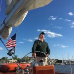 Captain of schooner at the helm on a bright blue sky day