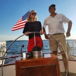 Young lady learning to steer the helm from one of our captains