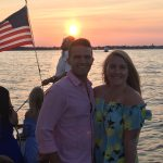 Smiling young couple on boat with American Flag and bright sunset