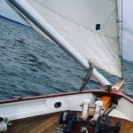 Bow of schooner with section of sail and boom and blue water ahead