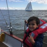 Happy little boy on boat with orange life vest