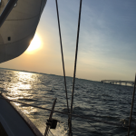 Sail and rigging of schooner with big yellow sun shining through
