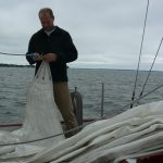 Crew member working on sail