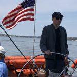 Young man steering the schooner with dark sunglasses on
