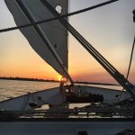 View from on board the schooner sailing straight at the setting sun